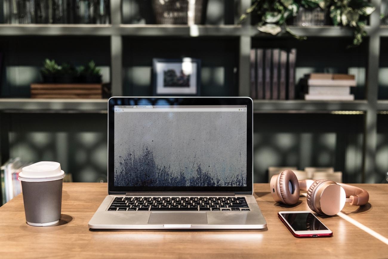 Laptop y computadora de escritorio sobre superficie de madera Descripción generada automáticamente
