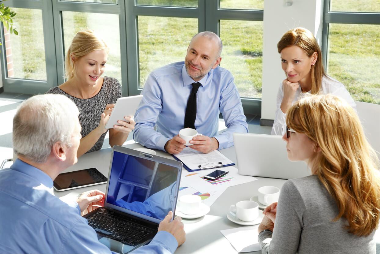 Un grupo de personas sentadas frente a una mesa con una computadora  Descripción generada automáticamente